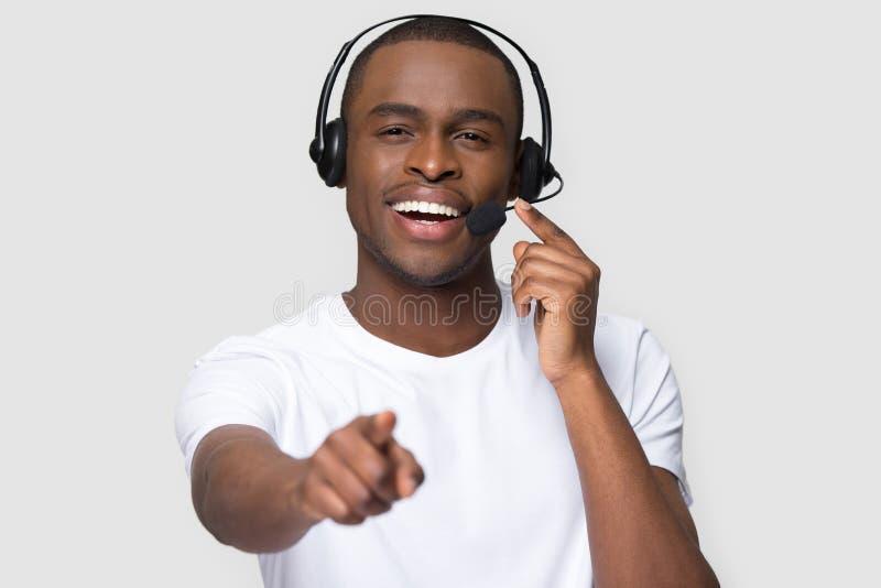 Homme africain de sourire dans le casque semblant dirigeant le doigt ? la cam?ra photo stock