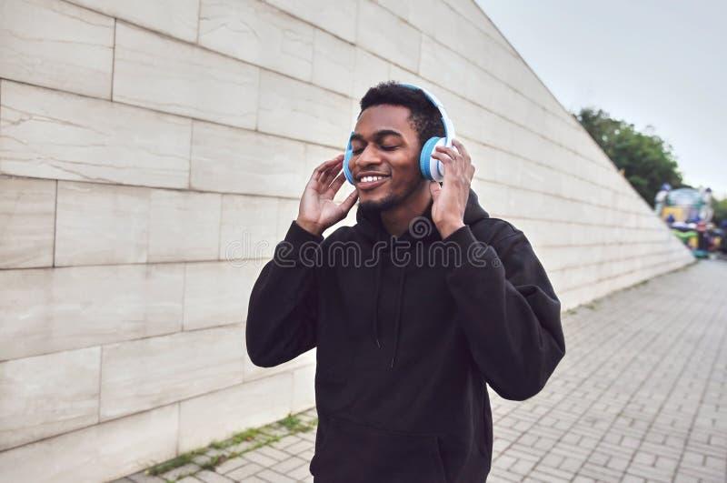 homme africain de sourire heureux urbain dans des écouteurs sans fil appréciant écouter la musique utilisant le hoodie noir sur l photographie stock libre de droits
