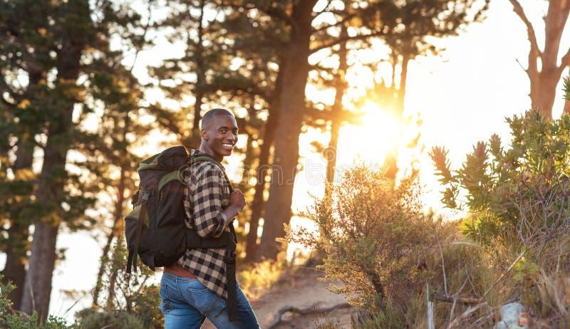Homme africain de sourire trimardant dans une forêt pendant l'après-midi photographie stock