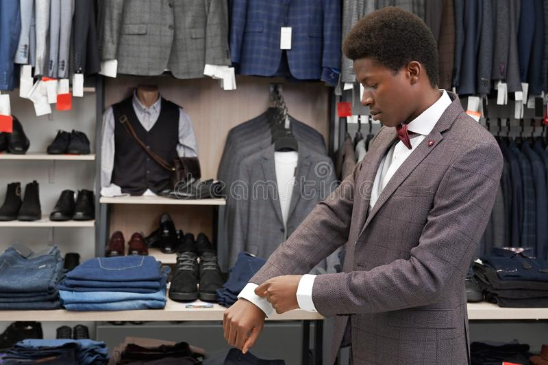 Homme africain essayant sur le costume dans la boutique, regardant la douille photographie stock