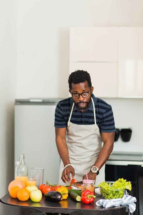 Homme africain préparant la nourriture saine à la maison dans la cuisine image libre de droits