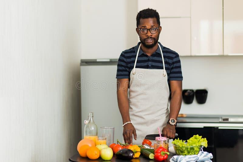 Homme africain préparant la nourriture saine à la maison dans la cuisine images libres de droits