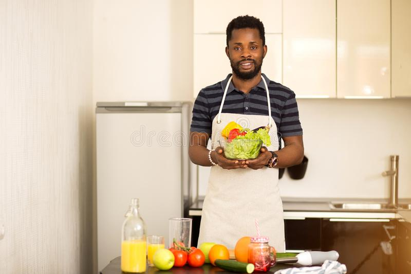 Homme africain préparant la nourriture saine à la maison dans la cuisine photographie stock libre de droits
