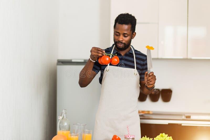 Homme africain préparant la nourriture saine à la maison dans la cuisine photo libre de droits