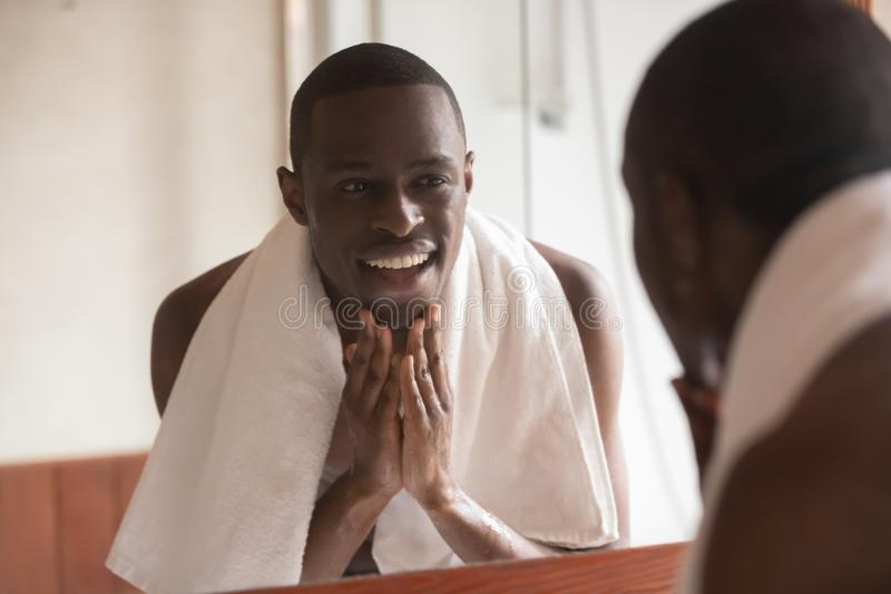 Homme africain regardant dans le visage de nettoyage de miroir après le rasage photos libres de droits