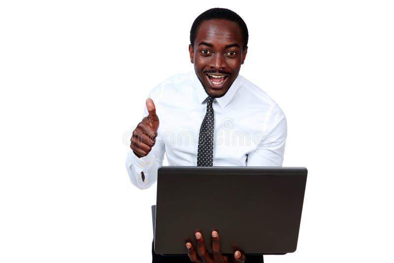 Homme africain riant tenant l'ordinateur portable image stock