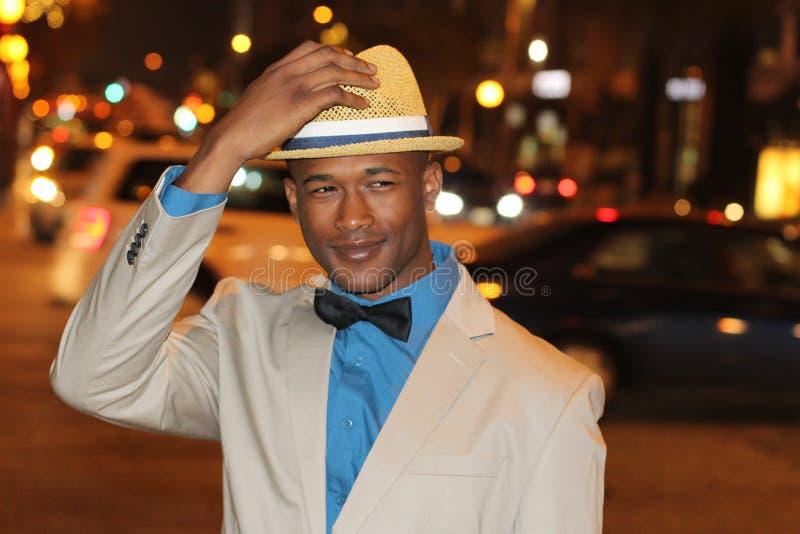 Homme africain sûr tenant le chapeau tout en marchant les rues de ville la nuit image libre de droits