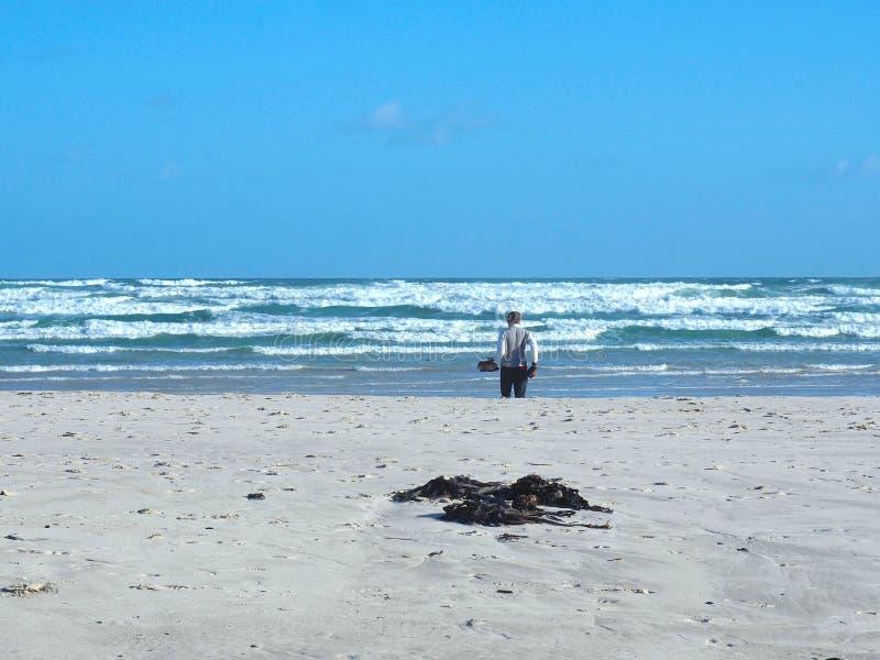 Homme africain tenant des chaussures et marchant sur la plage image libre de droits