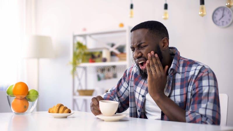Homme afro-américain ayant le mal dentaire, réaction sur le café chaud, dents sensibles photographie stock
