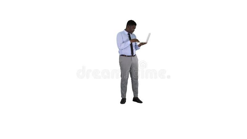 Homme afro-américain d'affaires travaillant avec l'ordinateur portable sur le fond blanc images stock