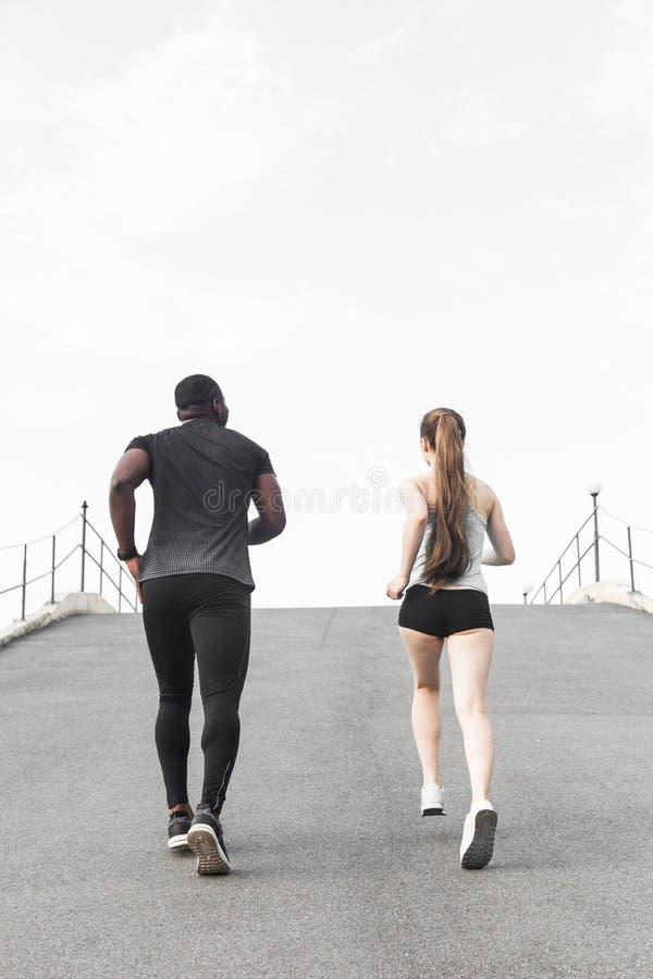 Homme afro-américain de jeunes couples heureux et femme européenne courant ensemble Un couple affectueux est couru, occupé dans l images stock