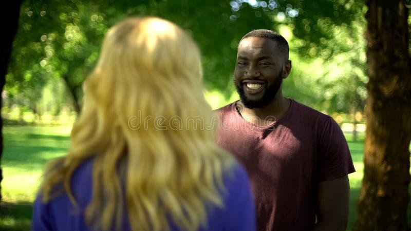 Homme afro-américain extrêmement heureux regardant la fille aimée, préparant la surprise photos libres de droits