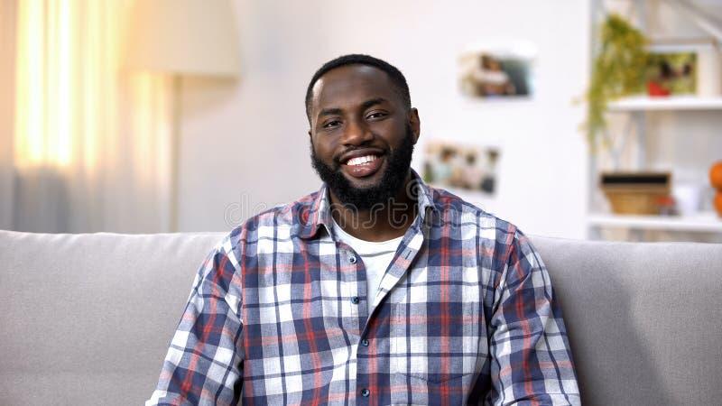 Homme afro-américain gai s'asseyant sur le sofa et regardant la caméra, détendant photographie stock