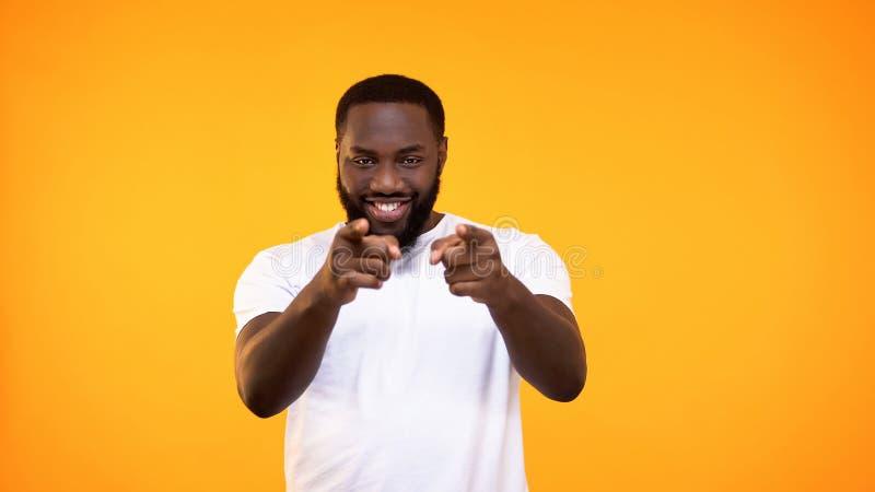 Homme afro-américain sûr dirigeant la caméra de doigts, geste bien choisi, signe de flirt photo stock