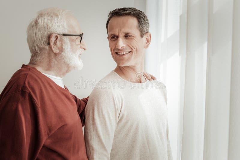 Homme agréable bel souriant et regardant son père image stock