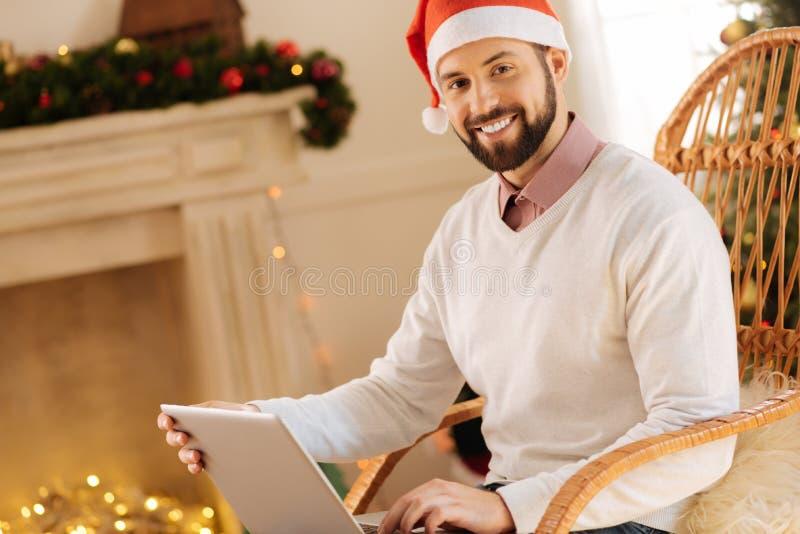 Homme agréable dans le chapeau de Santa posant avec l'ordinateur portable photographie stock