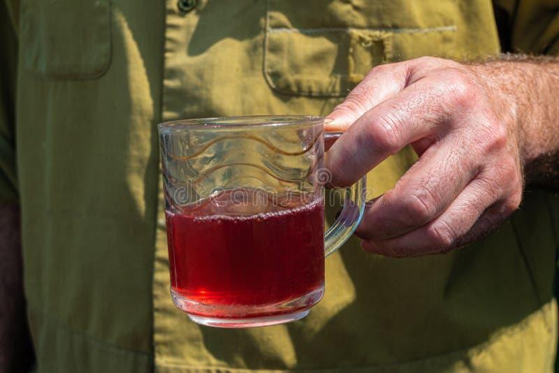Homme agraire simple et travaillant avec une tasse en verre de compote à la main photos libres de droits