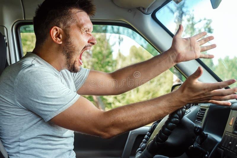 Homme agressif, le conducteur de la voiture est indigné au volant pendant le voyage Urgence, accident, violation des droits, diff photographie stock libre de droits