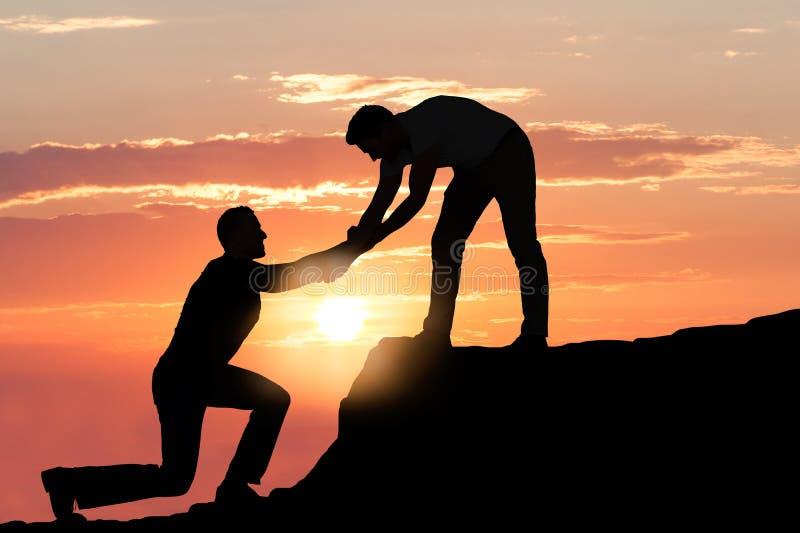 Homme aidant l'ami masculin dans la roche s'élevante pendant le coucher du soleil photos stock
