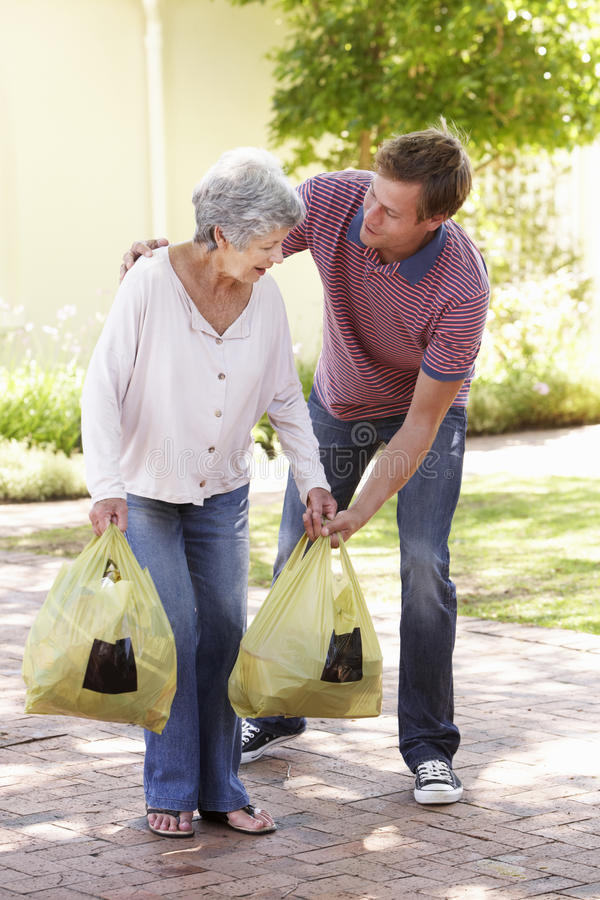 Homme aidant la femme supérieure avec des achats photo stock