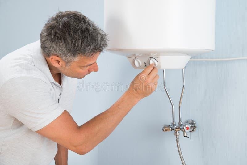Homme ajustant la température de la chaudière électrique photo libre de droits