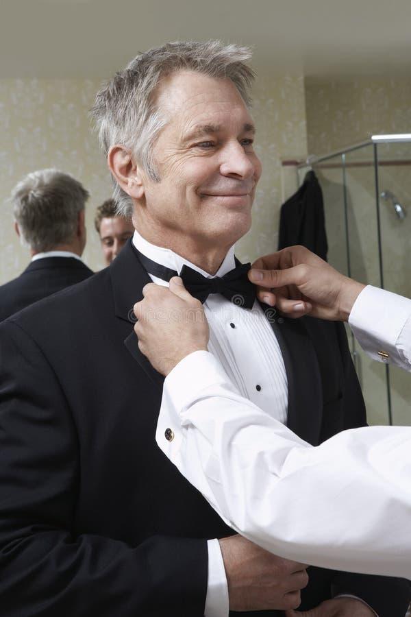 Homme ajustant le lien d'arc d'homme supérieur image stock