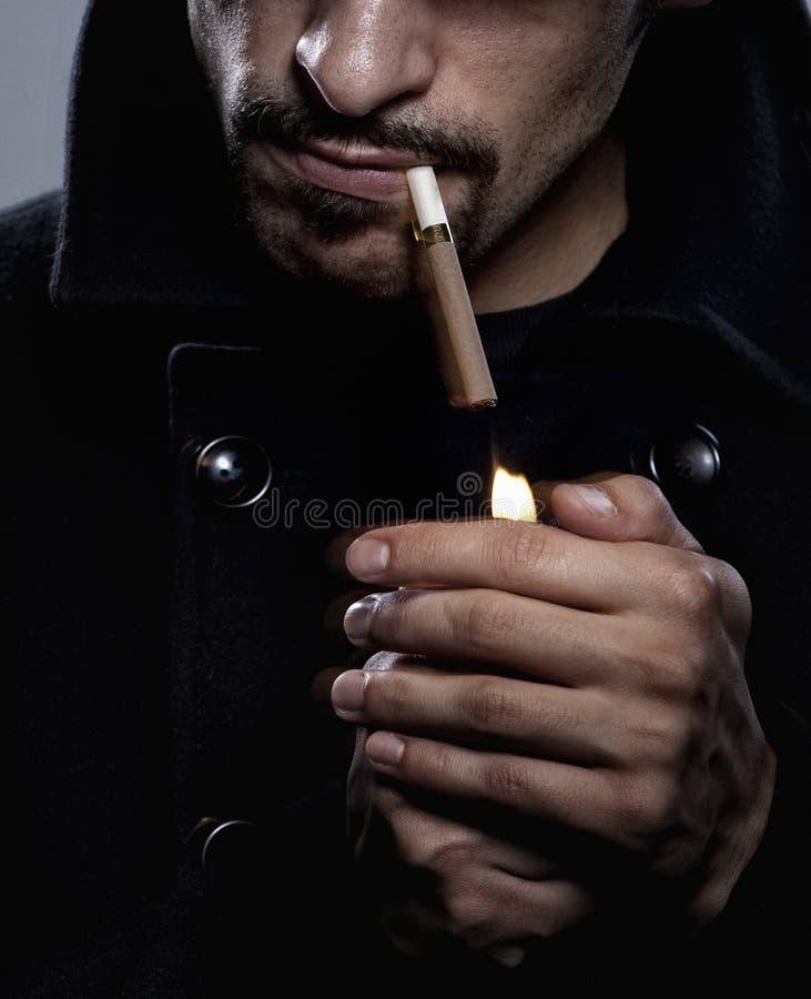 Homme allumant une cigarette photos stock