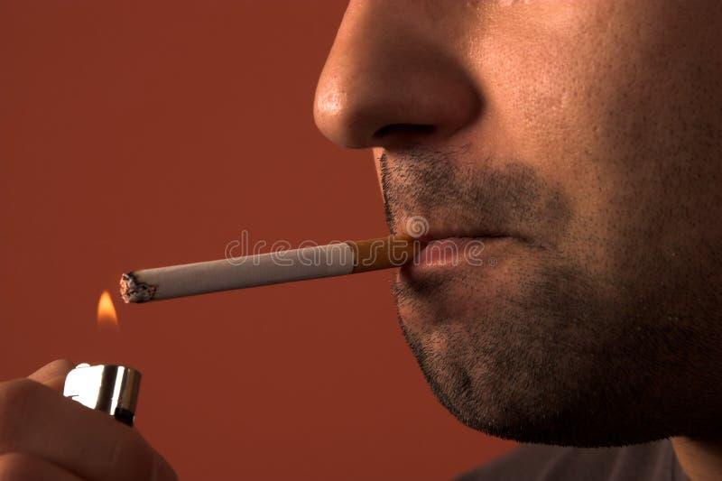 Homme allumant une cigarette photographie stock