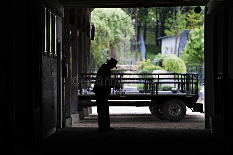Homme amish Silouetted dans sa sa porte de grange image stock