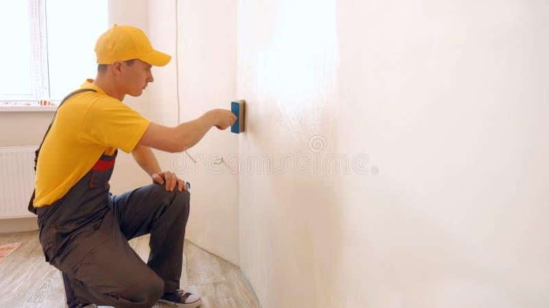 Homme appliquant la colle de papier peint utilisant une brosse photographie stock libre de droits