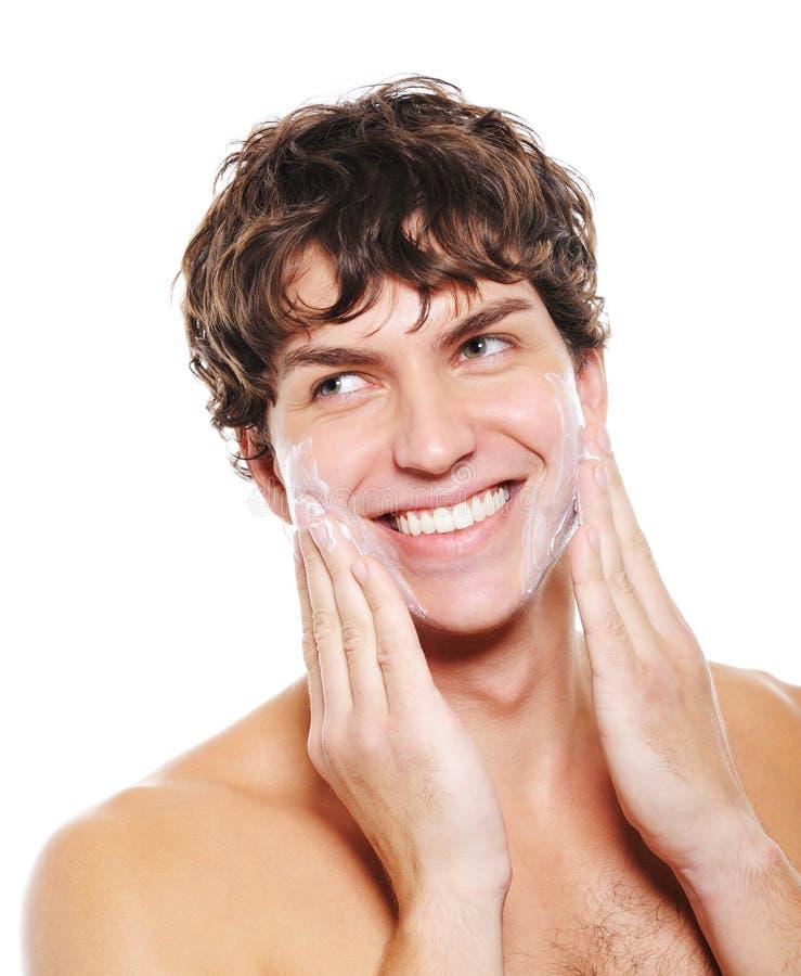 Homme appliquant la crème d'hydratation après avoir rasé photographie stock