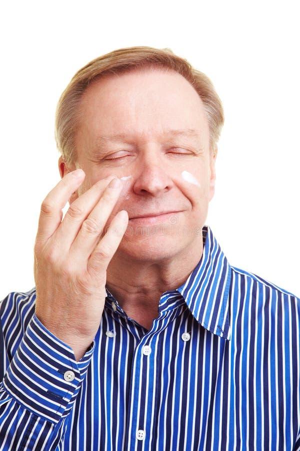 Homme appliquant la lotion à son visage photographie stock