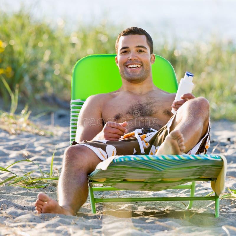 Homme appliquant la lotion de protection solaire à la plage images libres de droits