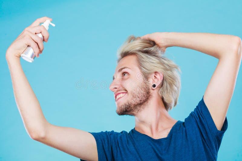 Homme appliquant le cosmétique de jet à ses cheveux photo stock