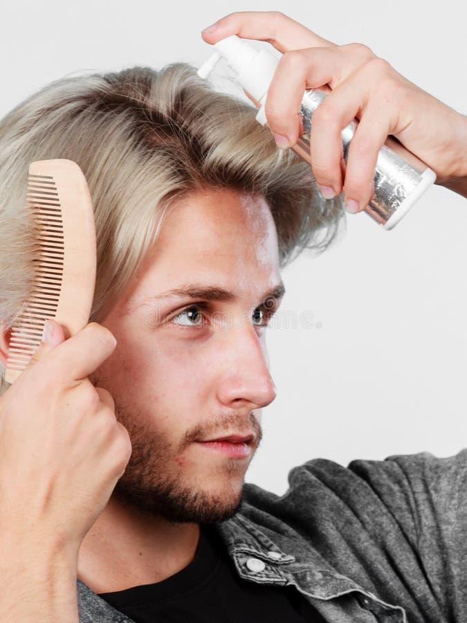 Homme appliquant le cosmétique de jet à ses cheveux photo libre de droits