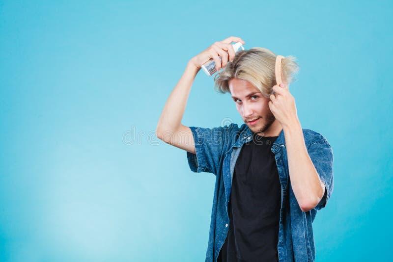 Homme appliquant le cosmétique de jet à ses cheveux image libre de droits