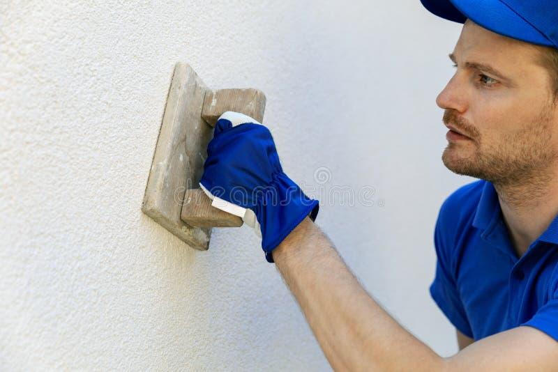 homme appliquant le plâtre décoratif de façade avec la truelle sur l'extérieur de maison photo stock