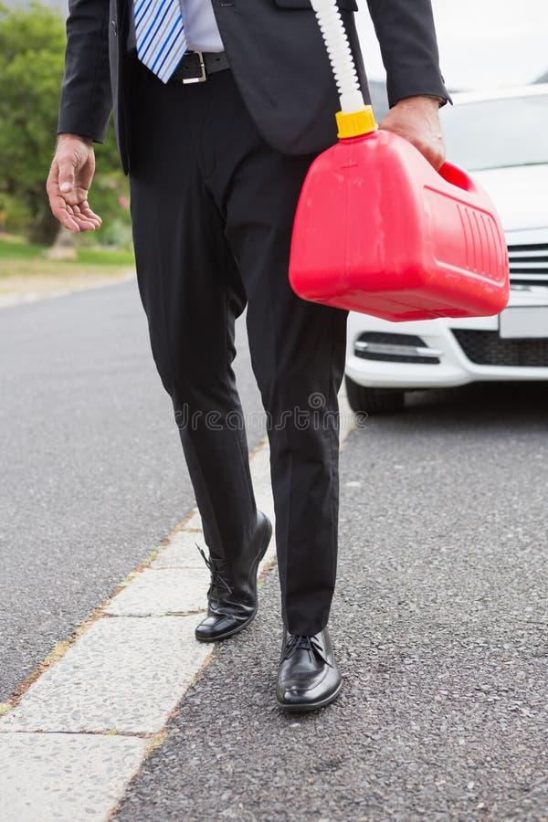 Homme apportant la boîte métallique d'essence après décomposé photo stock