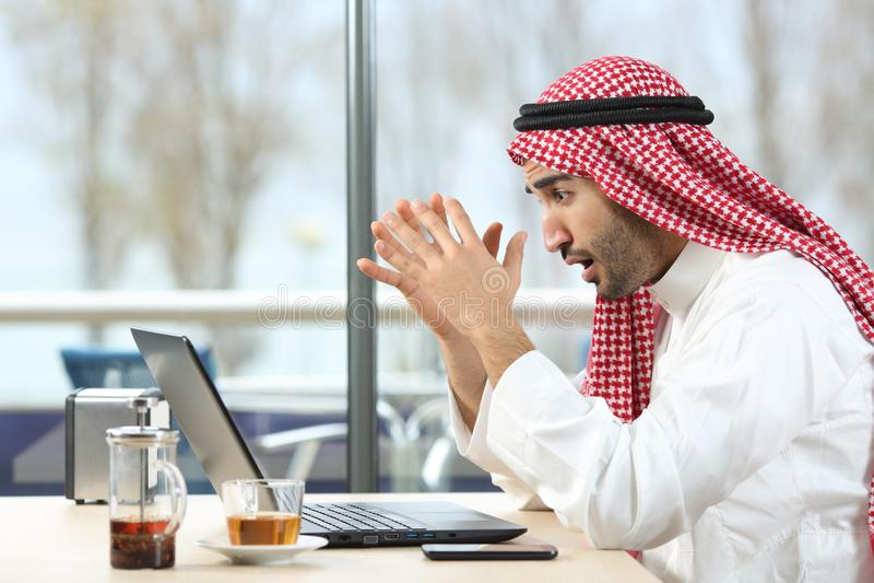 Homme arabe choqué vérifiant l'ordinateur portable dans une barre photos libres de droits