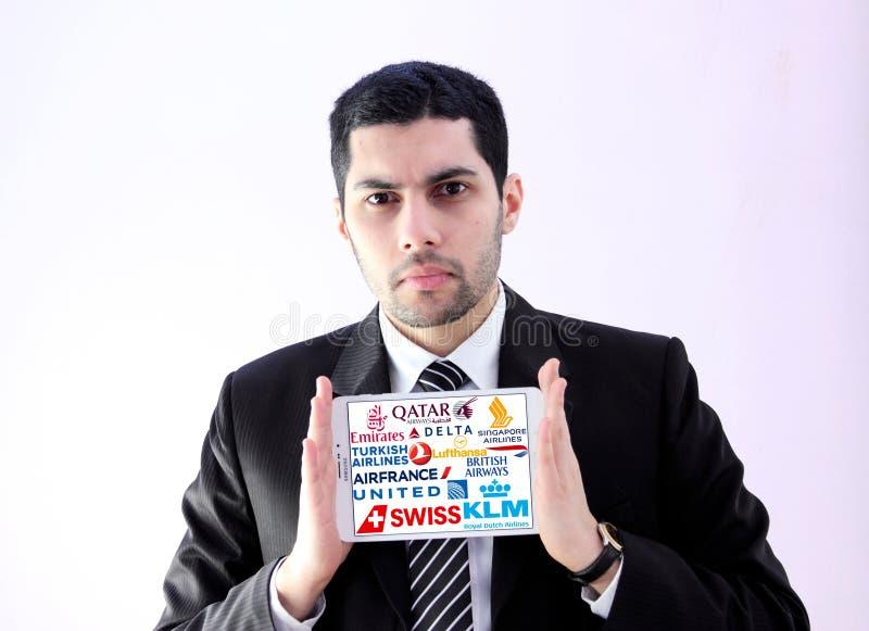Homme arabe d'affaires avec des lignes aériennes et des logos célèbres de voies aériennes photo libre de droits
