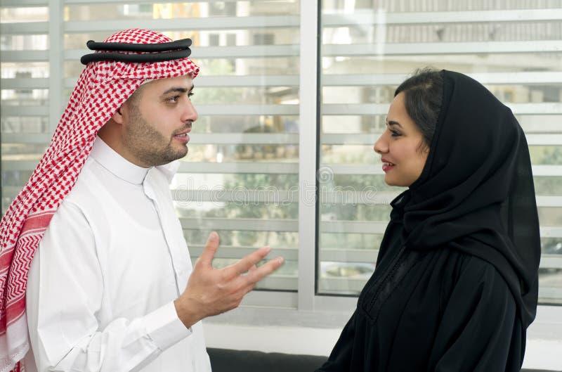 Homme Arabe d'affaires ayant une discussion avec une femme d'affaires Arabe dans le bureau image stock