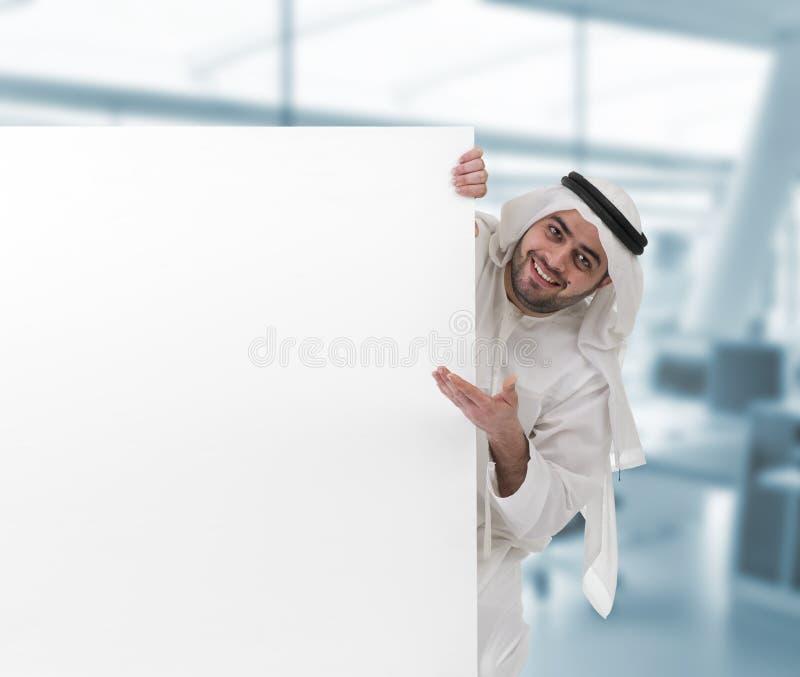Homme Arabe d'affaires se dirigeant à un signe blanc photo stock