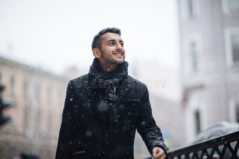 Homme arabe joyeux dans la ville d'hiver photos stock