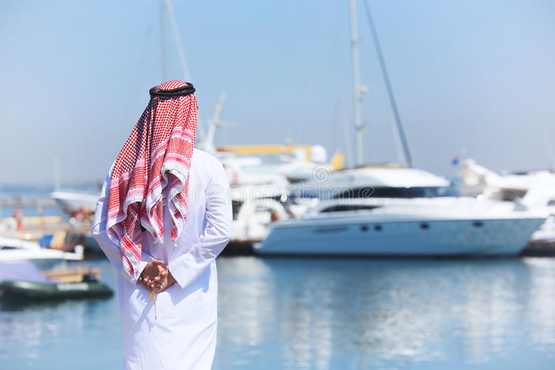 Homme Arabe regardant le port de yacht image stock