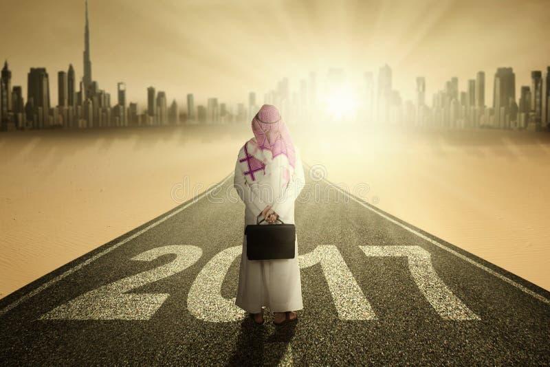 Homme arabe se tenant sur la route avec 2017 photo stock