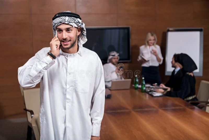 Homme Arabe semblant heureux tenant un téléphone images libres de droits