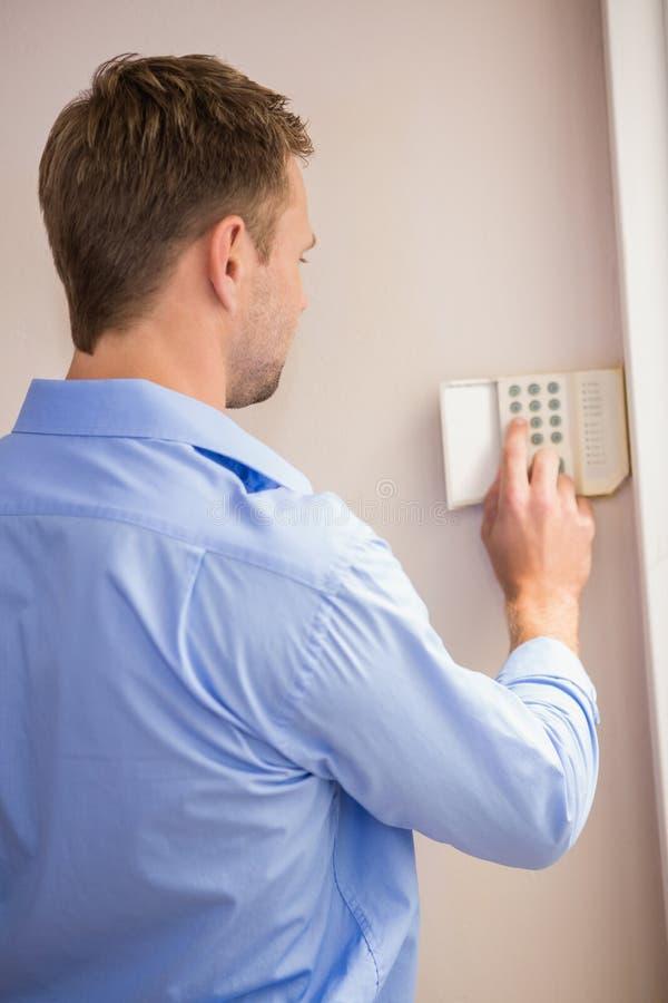 Homme armant une alarme à la maison image libre de droits