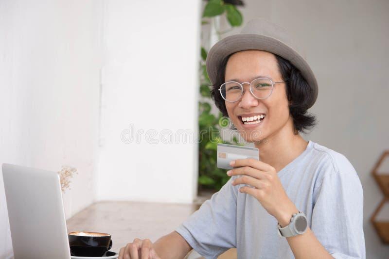 Homme asiatique avec le chapeau de padora souriant et employant la carte de crédit ou la carte de débit images libres de droits
