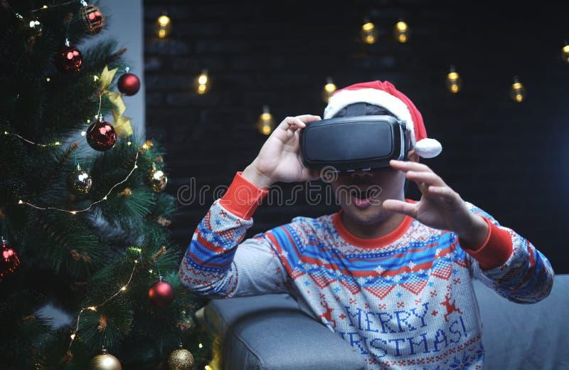 Homme asiatique avec le costume de Noël jouant se reposer de réalité virtuelle photo stock