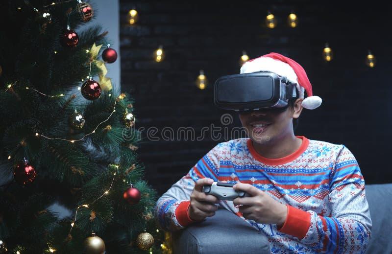 Homme asiatique avec le costume de Noël jouant se reposer de réalité virtuelle image libre de droits